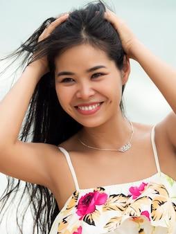 Porträt der jungen schönen asiatischen frau, die draußen lächelt und geht. mädchen berührt ihre haare. sommerzeit, entspannung oder urlaubskonzept