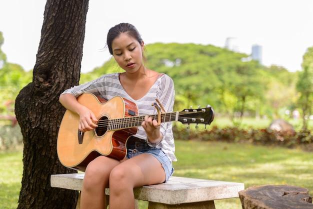 Porträt der jungen schönen asiatischen frau, die gitarre am park draußen spielt