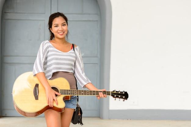 Porträt der jungen schönen asiatischen frau, die gitarre in den straßen der stadt draußen spielt
