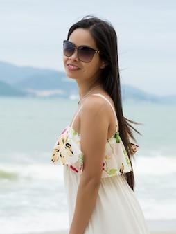 Porträt der jungen schönen asiatischen frau, die sonnenbrille trägt und am strand steht. sommerzeit, entspannung oder urlaubskonzept