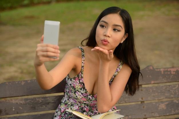 Porträt der jungen schönen asiatischen frau videoanruf mit telefon im park