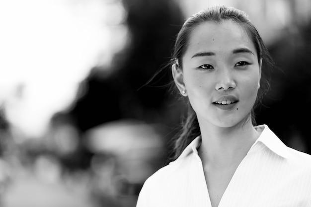 Porträt der jungen schönen asiatischen geschäftsfrau in den straßen draußen in schwarzweiss