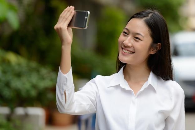 Porträt der jungen schönen asiatischen geschäftsfrau in den straßen draußen