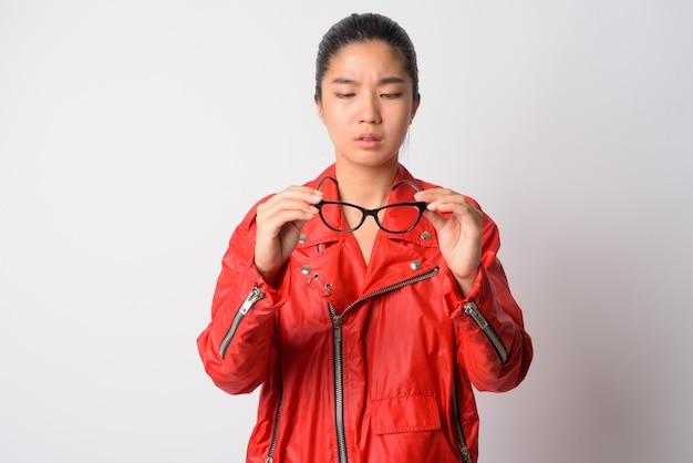 Porträt der jungen schönen asiatischen rebellischen frau gegen weiße wand