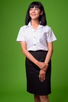 Porträt der jungen schönen asiatischen studentin gegen grüne wand