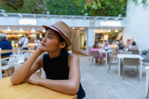 Porträt der jungen schönen asiatischen touristenfrau am restaurant im freien in spanien