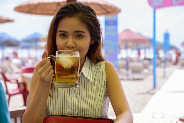 Porträt der jungen schönen asiatischen touristenfrau, die am restaurant am strand draußen sitzt