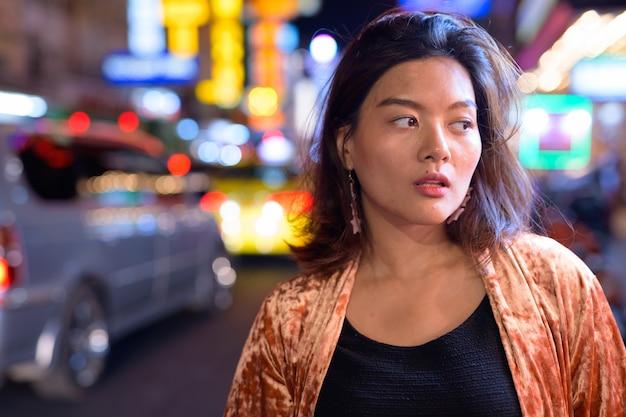 Porträt der jungen schönen asiatischen touristenfrau, die chinatown in bangkok erkundet