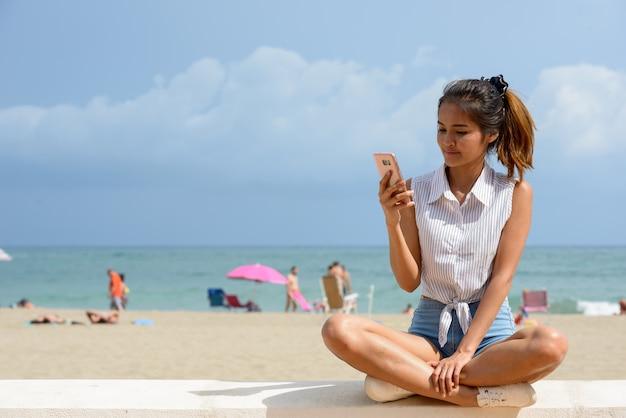 Porträt der jungen schönen asiatischen touristenfrau, die draußen am strand sitzt