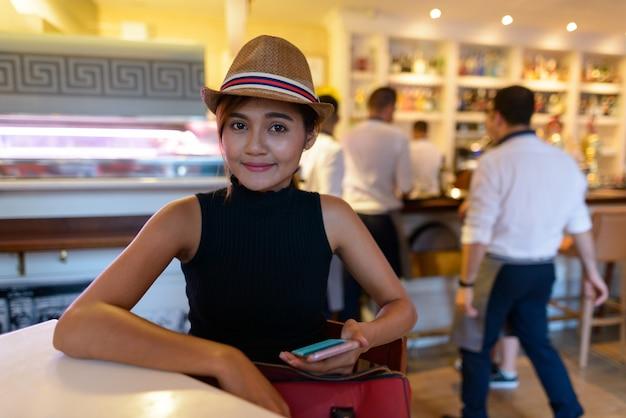 Porträt der jungen schönen asiatischen touristenfrau, die innerhalb des restaurants in spanien sitzt