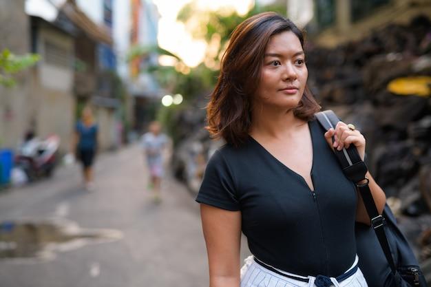 Porträt der jungen schönen asiatischen touristenfrau in den schmutzigen gassen von bangkok Premium Fotos