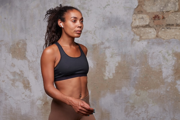 Porträt der jungen schönen athletischen dunkelhäutigen lockigen sportlerin mit kopfhörern in ihren ohren, die über mauer gehen