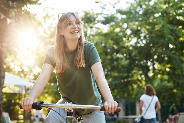 Porträt der jungen schönen blonden frau, die genießt, so zu tun, als würde sie ein fahrrad im park während eines lebensmittelfestivals fahren