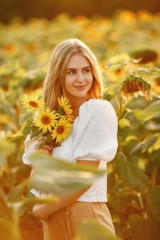 Porträt der jungen schönen blonden frau im sonnenblumenfeld im gegenlicht. sommerlandschaftskonzept. frau und sonnenblumen. sommerlicht. schönheit im freien.
