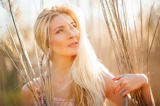 Porträt der jungen schönen blonden lächelnden frau im gelben gras, das an klarem sonnigem tag beiseite schaut