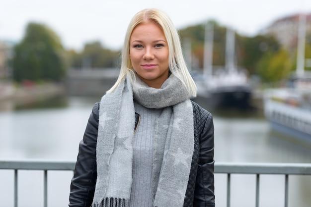 Porträt der jungen schönen blonden skandinavierin, die sich am fluss entspannt