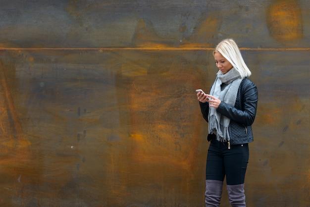 Porträt der jungen schönen blonden skandinavischen frau gegen rostige alte metallwand im freien