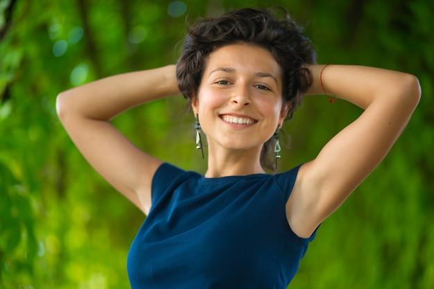 Porträt der jungen schönen brünette genießen, im grünen sommerpark spazieren zu gehen