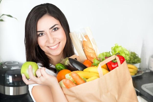 Porträt der jungen schönen brünetten frau, die auf ihrer küche mit gerade gelieferter großer papiertüte voll des vegetarischen essens steht und grünen apfel hält