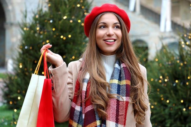 Porträt der jungen schönen frau beim einkaufen an heiligabend