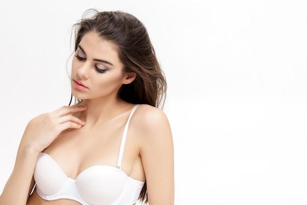 Porträt der jungen schönen frau brünette mit natürlichem make-up in den weißen dessous