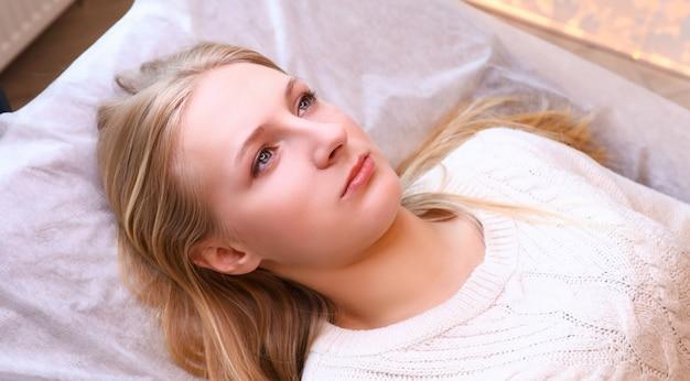 Porträt der jungen schönen frau, die auf kosmetikertisch liegt. hellhaarige frau, die sich auf die gesichtsbehandlung vorbereitet. wellness- und schönheitssalonkonzept