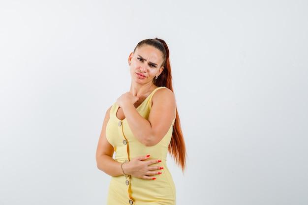 Porträt der jungen schönen frau, die aufwirft, während sie im kleid steht und die verärgerte vorderansicht schaut