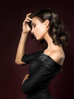 Porträt der jungen schönen frau, die das schwarze abendkleid trägt, das über dunkelrotem hintergrund aufwirft