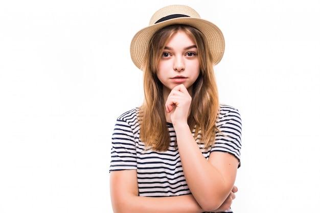 Porträt der jungen schönen frau, die davon träumt, über die weiße wand die stirn zu runzeln
