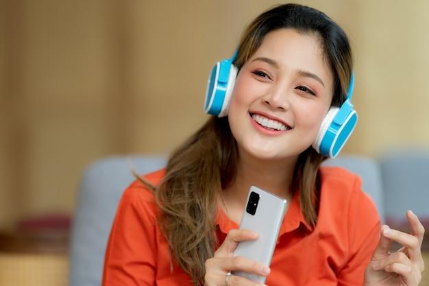 Porträt der jungen schönen frau, die die musik mit smileygesicht im kreativen büro oder im café genießt