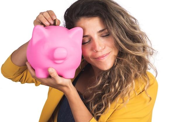 Porträt der jungen schönen frau, die ein sparschwein auf studio hält. isolierter weißer hintergrund. sparen sie geld konzept.