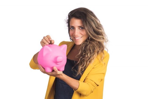 Porträt der jungen schönen frau, die ein sparschwein auf studio hält. sparen sie geld konzept.