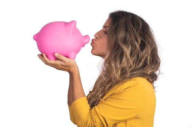 Porträt der jungen schönen frau, die ein sparschwein auf studio hält und küsst. isolierter weißer hintergrund. sparen sie geld konzept.