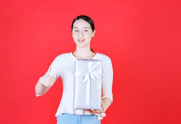 Porträt der jungen schönen frau, die geschenkbox hält und daumen nach oben gestikuliert