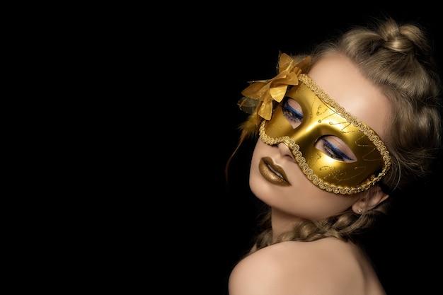 Porträt der jungen schönen frau, die goldene parteimaske trägt. karneval in venedig, maskenball oder neujahrsparty.
