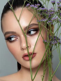 Porträt der jungen schönen frau, die hinter einem zweig der violetten blumen steht