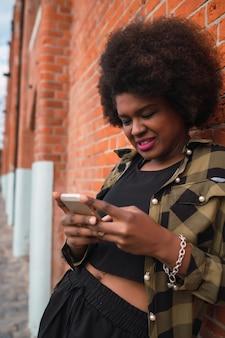 Porträt der jungen schönen frau, die ihr handy draußen in der straße benutzt. stadt- und kommunikationskonzept.