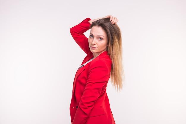 Porträt der jungen schönen frau, die im roten anzug mit hand oben aufwirft.