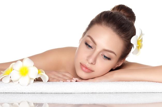 Porträt der jungen schönen frau, die im spa-salon lokalisiert liegt. spa-therapie-, hautpflege-, erholungs- und kosmetikkonzept