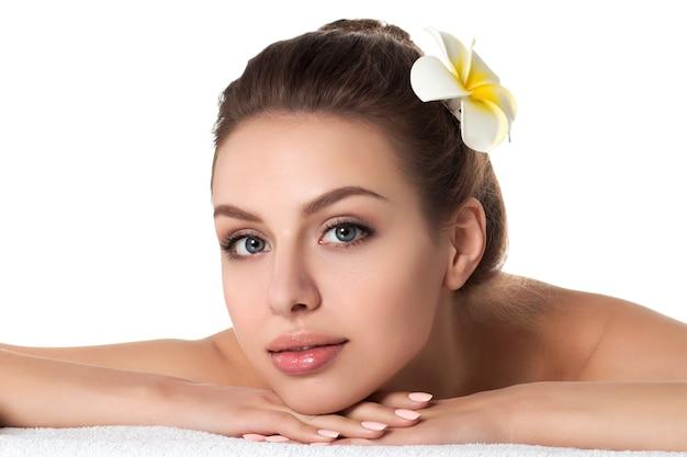 Porträt der jungen schönen frau, die im spa-salon lokalisiert liegt