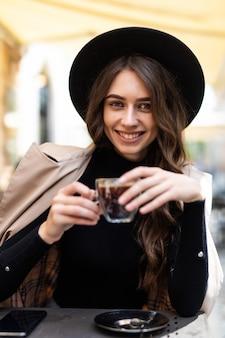 Porträt der jungen schönen frau, die in einem café draußen kaffeetrinkend sitzt