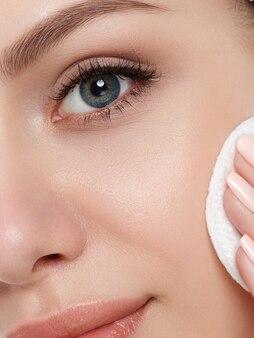 Porträt der jungen schönen frau, die make-up von ihrem gesicht mit kosmetikkissen reinigt. reinigungsgesicht, perfektes haut-, hautpflege- und kosmetikkonzept. extreme nahaufnahme, teilweise gesichtsansicht