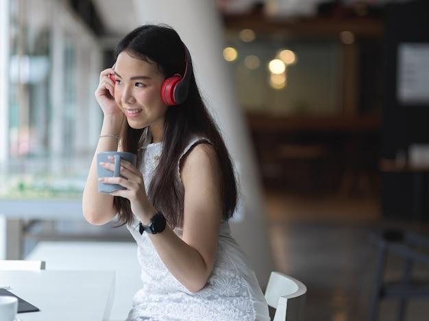 Porträt der jungen schönen frau, die mit kopfhörer und kaffeetasse im gemeinsamen arbeitsraum entspannt
