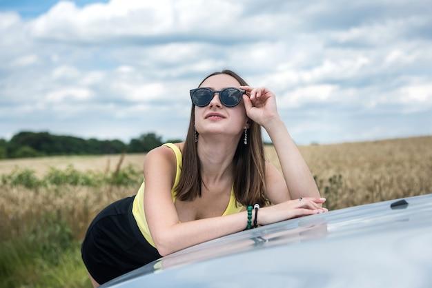 Porträt der jungen schönen frau, die nahe ihrem auto an der landstraße steht. traum für die perfekte reise im sommer