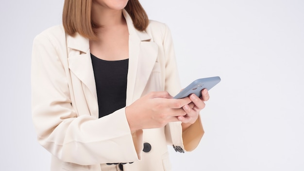 Porträt der jungen schönen frau im anzug mit smartphone auf weißem hintergrund
