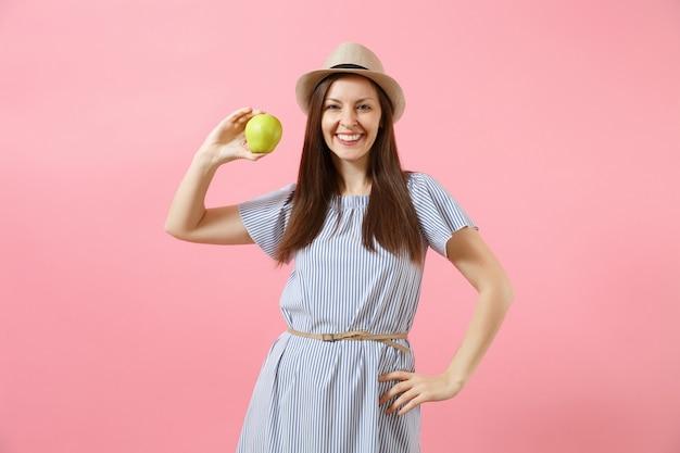 Porträt der jungen schönen frau im blauen kleid, sommerstrohhutholding, grüne frische apfelfrucht einzeln auf rosafarbenem hintergrund essend. gesunder lebensstil, menschen, konzept der aufrichtigen emotionen. platz kopieren.
