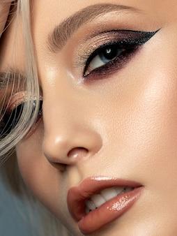 Porträt der jungen schönen frau mit abend make-up. moderner mode eyeliner flügel. nahaufnahme, teilweise gesichtsansicht