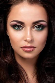Porträt der jungen schönen frau mit abend make-up posiert. rot und gold mehrfarbige rauchige augen. luxus-hautpflege und modernes mode-make-up-konzept.