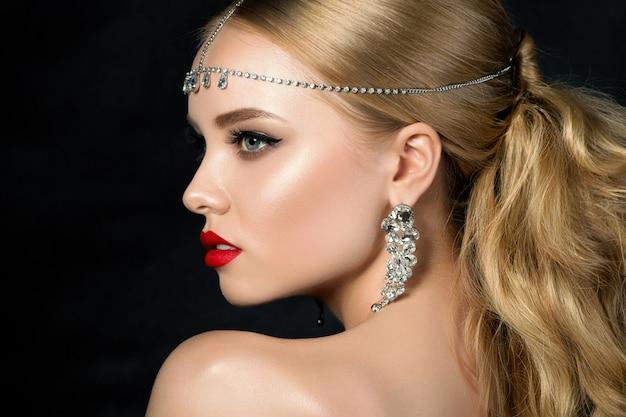 Porträt der jungen schönen frau mit abend make-up über die schulter schauen. model posiert. rote lippen und eyeliner. klassisches make-up-konzept ..