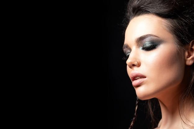 Porträt der jungen schönen frau mit dem abendlichen make-up-modell, das über schwarzem hintergrund aufwirft